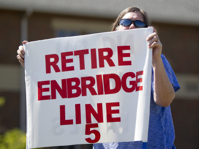 A woman holds a protest sign against Enbridge's Line 5 in Michigan in 2017.